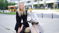 Happy businesswoman sitting on scooter