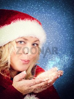 Joyful pretty woman blowing stars in red santa claus hat