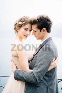 Newlyweds hug against the backdrop of Lake Como. Close up