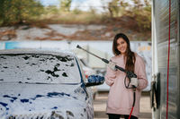 Brunette from a high-pressure hose applies a cleaner on the car