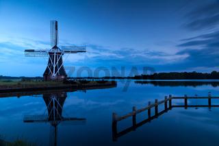 windmill close to lake at dusk