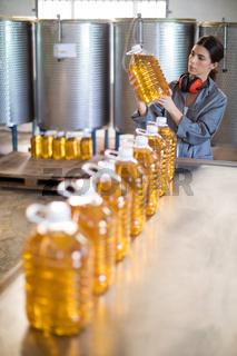 Female worker checking oil bottles