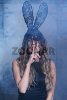 Young blonde woman in black rabbit or hare fancy mask and black dress. Finger on lips. Female on smoke and metal wall background.