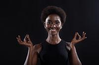 Studio portrait of african american female model showing zen or okay sign gesture. Woman meditating on black background.