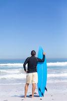 Senior Caucasian man holding a surfboard at the beach.