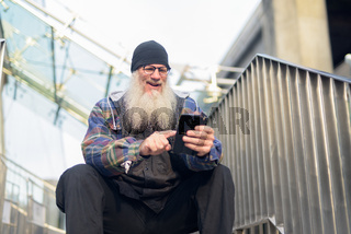 Happy mature bearded hipster man using phone at footbridge