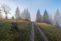 Foggy autumn mountain sunrise scene. Peaceful picturesque traveling, seasonal, nature and countryside beauty concept scene.