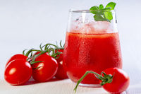 Tomato juice with ice cubes in a glass.