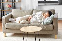 pregnant asian woman sleeping on sofa at home