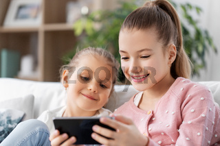 happy little girls or sisters with phone at home
