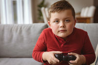 Caucasian boy playing video games sitting on the couch at home