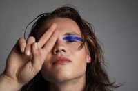 Young caucasian guy with creative make-up posing in the studio.