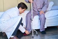 Altenpfleger hilft Senior beim Schuhe anziehen im Pflegeheim