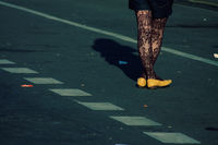 Female legs, yellow shoes, tights, street