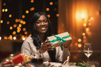 happy african woman with christmas gift at home