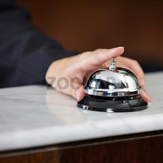 Weibliche Hand läutet Hotelglocke