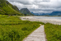 A wooden footpath leads through a green gras meadow to a white sand beach with clear water and mountains behind