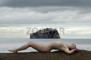 Junge nackte Frau auf Felsen vor dem Bass Rock in Irland