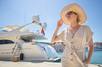 Young woman at the pier with sailing yachts. A beautiful girl enjoing vacation in front of moored sport yachts on a hot sunny summer day