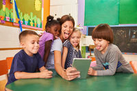Kinder und Erzieherin zeigen die Zunge für ein Selfie