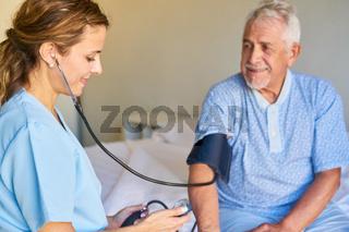 Krankenschwester mit Stethoskop misst sorgfältig den Blutdruck