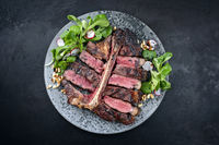 Modern style traditional barbecue dry aged wagyu porterhouse beef steak bistecca alla Fiorentina with corn salad and pine nuts served as top view on a Nordic design plate