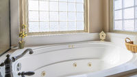 Pano Built in round bathtub inside bathroom with floral curtains on the windows