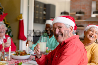 Happy caucasian senior man holding glass and celebrating christmas with diverse group of friends