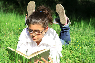 girl laying on grass reading book outdoors in summer on campus