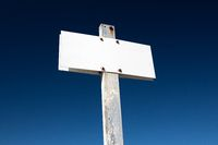 Blank white sign isolated on dramatic blue sky. Aged metallic post sign. Template Mock up
