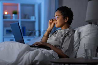 woman with laptop in bed at home at night