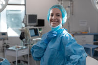 Portrait of caucasian female surgeon standing in operating theatre wearing face mask