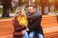 happy loving couple embracing sitting on the bench romantic hugged in park wearing coats and scarfs Collecting a bouquet of fallen leaves. Love story concept. Tinted image