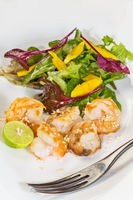 Fresh salad with fried shrimps, variety of salad leafs, mango, orange, and toasted sesame