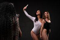 Attractive diverse women in studio taking selfie smartphone