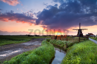 warm sunrise over Dutch windmill  and river