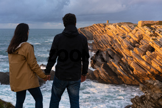 Couple caucasian female and male holding hands looking at cliff landscape with ocean waves in Baleal Island, Peniche, Portugal