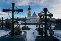 Village church seen through tomb crosses at snow covered graveyard, Wildermieming, Austria