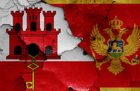 flags of Gibraltar and Montenegro painted on cracked wall