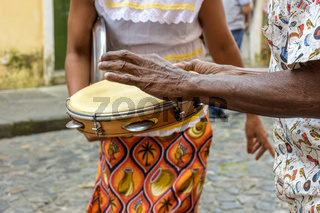 Tambourine player hands with a woman in typical clothes dancing in the background