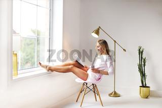 Happy young female reading magazine near window