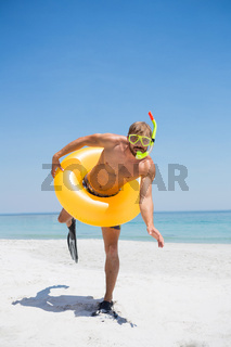 Playful man with snorkel wearing inflatable ring