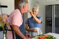 Happy caucasian senior couple standing in kitchen, preparing meal together and eating vegetables