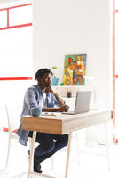 African american male painter at work using laptop in art studio