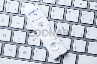 Covid-19 rapid antigen test. Rapid antibodies test kit and computer keyboard.