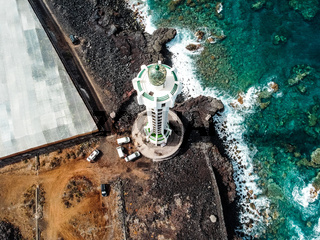 Aerial top view of lighthouse, rocks and ocean waves in a volcanic landscape