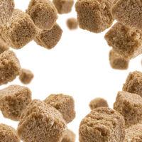 Brown cane sugar levitates on a white background