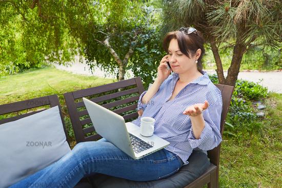 Freelancer Frau im Garten mit Laptop PC beim Telefonat