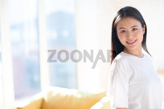 Portrait of smiling asian woman on apartment interior background