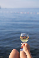 A girl holds a glass of white wine in her hand against the backdrop of a beautiful blue sea. Holiday and vacation concept. Place for an inscription.